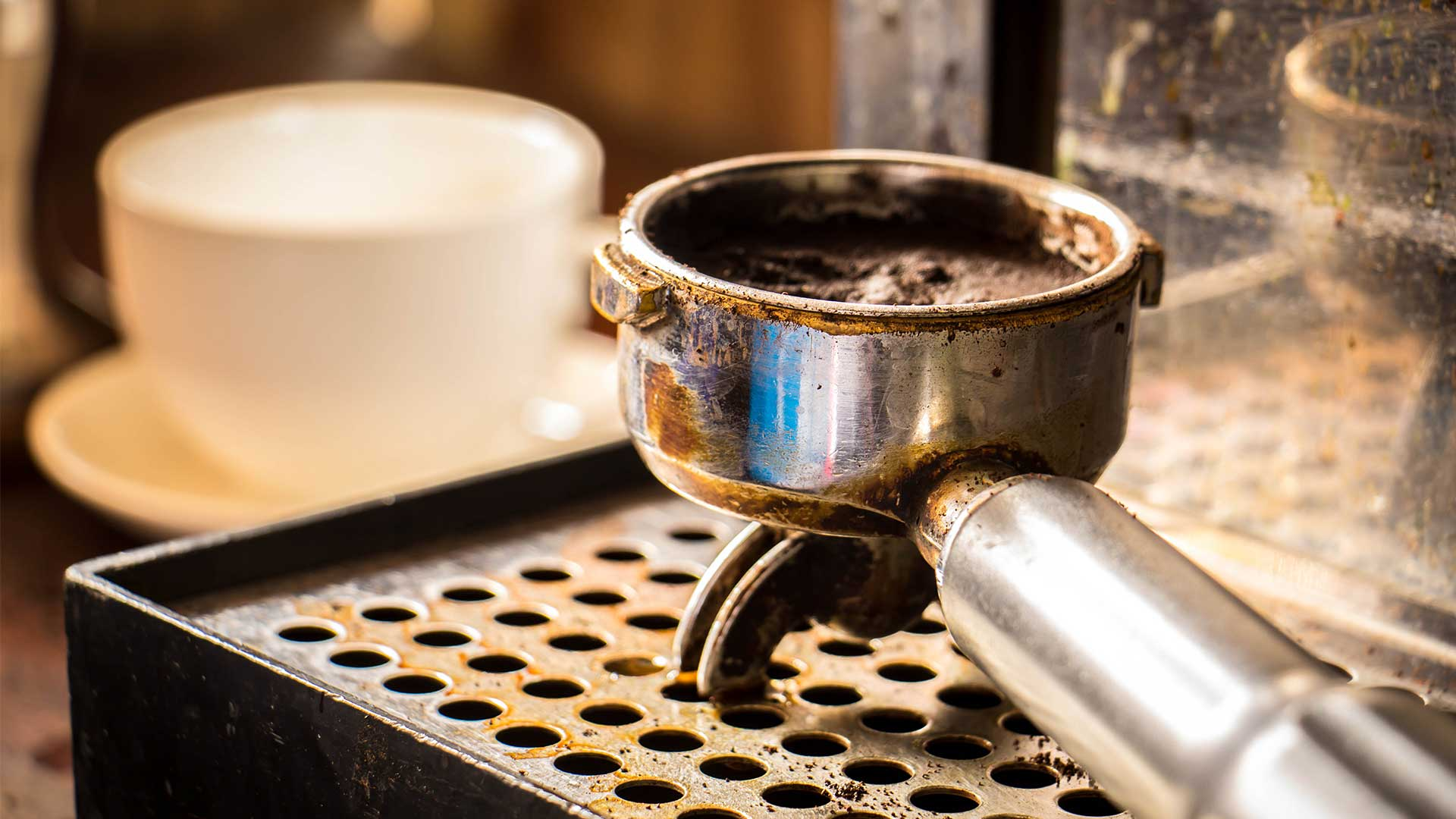 A coffee handle with the the basket full of spent grounds sits on the drop tray of an espresso machine.