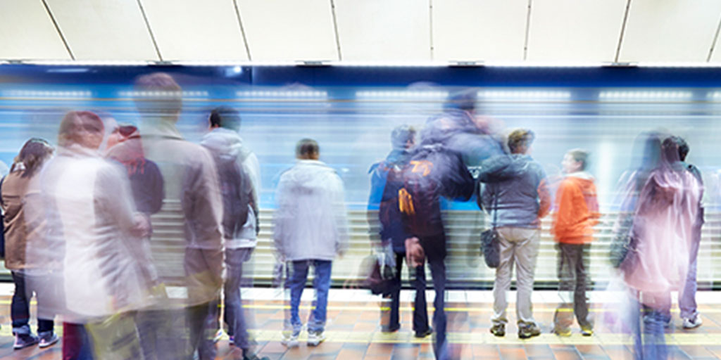 Long exposure photograph showing blurred commuters and a train at a train station.