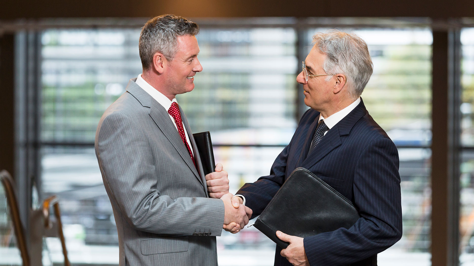 A businessman shakes hands with a Victorian Government representative.