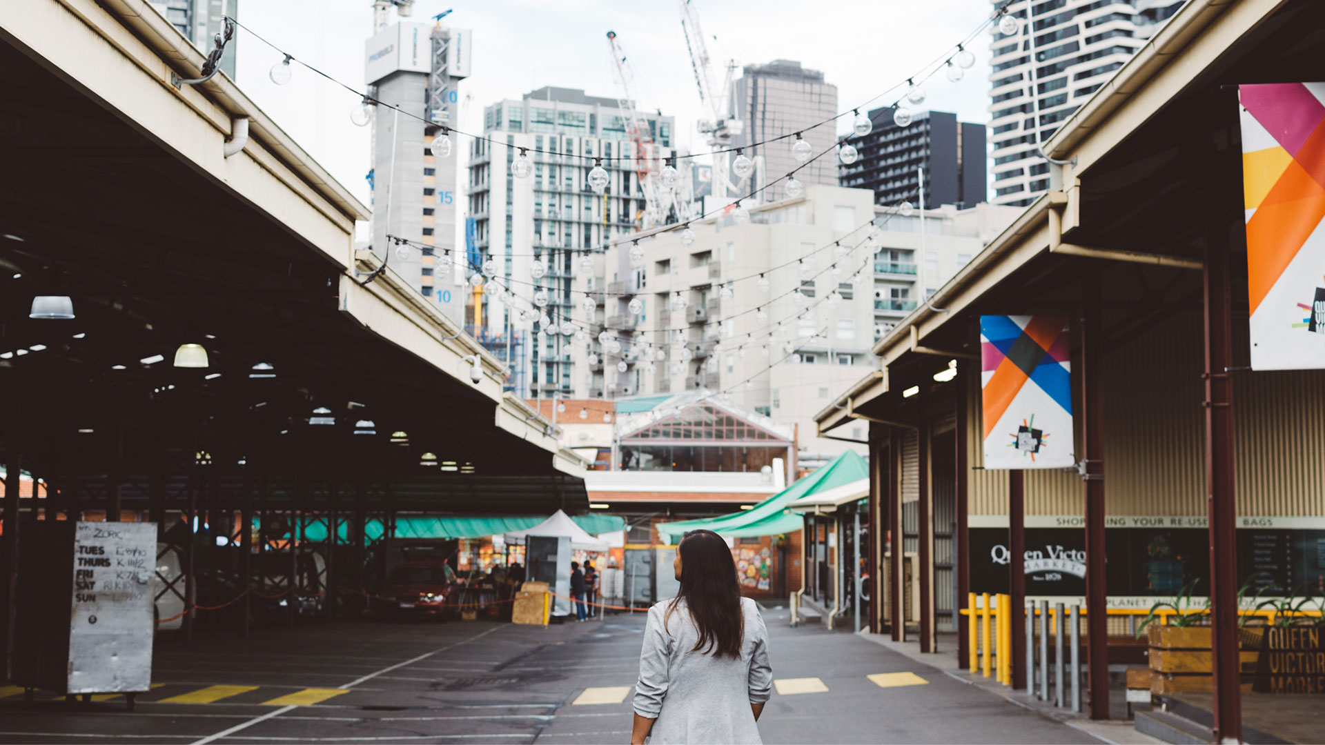 A woman stands in Queen Victoria Market with the Melbourne skyline in the background