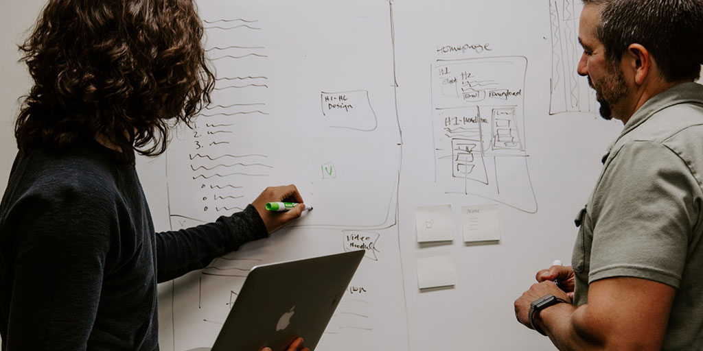 A woman holding a laptop and a man work on website planning n a whiteboard