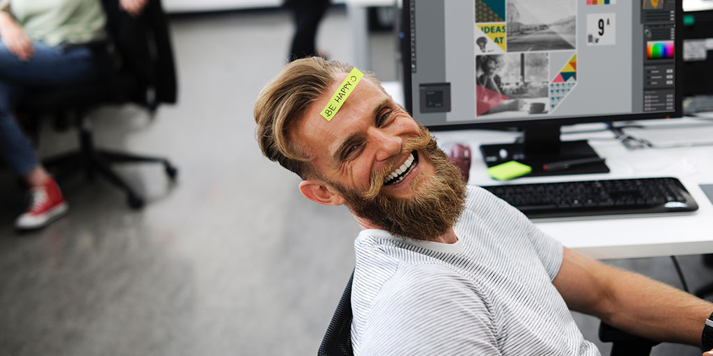 A bearded man smiles at the camera. A Post It note on his forehead reads 'BE HAPPY : )