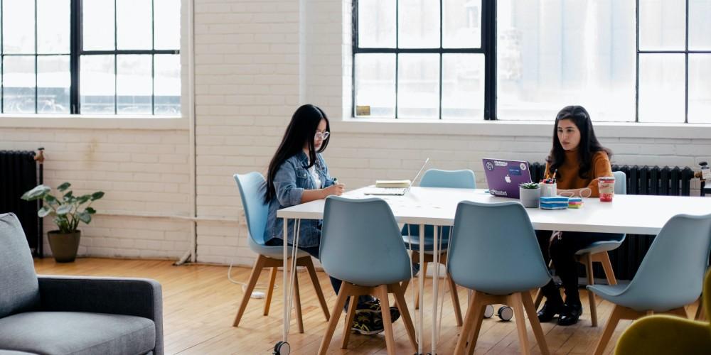 Two women working on laptops in a studio