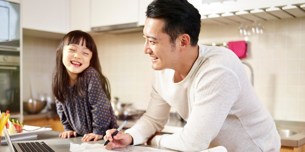 Young father working at kitchen bench with his young daughter beside him