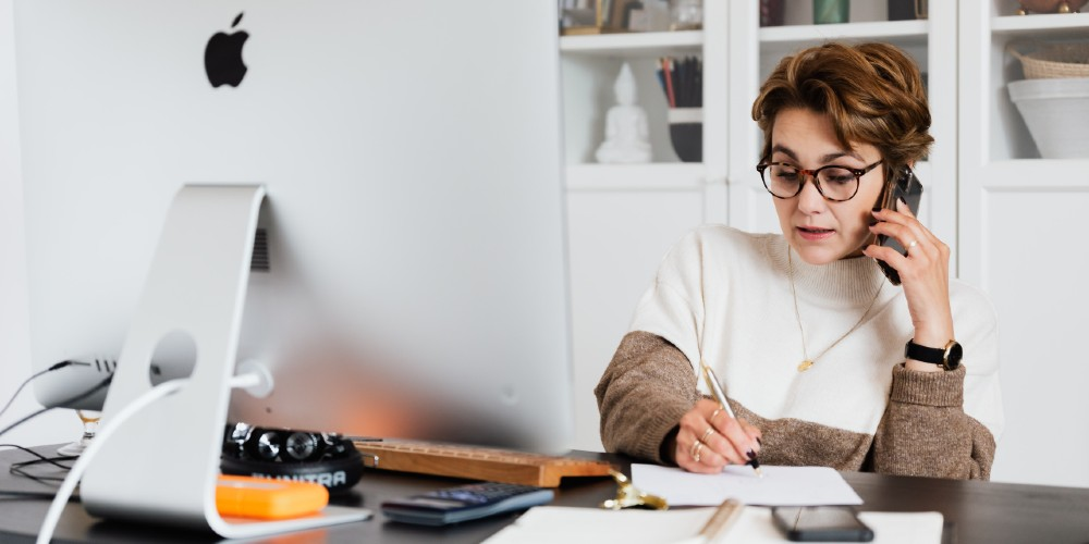Woman at desk taking notes while on the phone